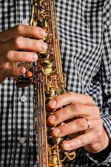 Sopransaxophon in den händen auf einem schwarzen hintergrund