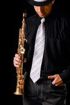 Sopransaxophon in den händen eines mannes auf einer schwarzen oberfläche