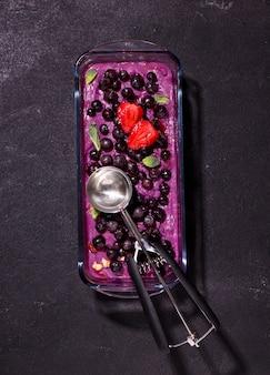 Sorbet aus ube und schwarzen johannisbeeren, verziert mit erdbeerschnitten auf einem schwarzen feld