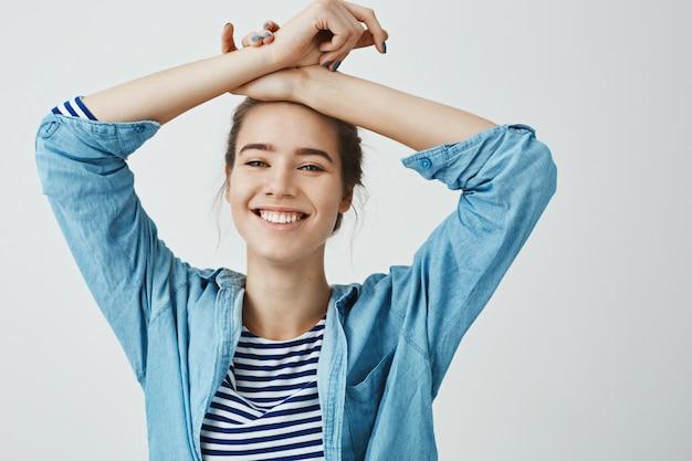 Sorge dich nicht, sei glücklich. porträt einer wunderschönen verliebten freundin, die verschränkte arme auf der stirn hält, in sinnlicher pose steht, breit lächelt und positive und zarte gefühle ausdrückt.
