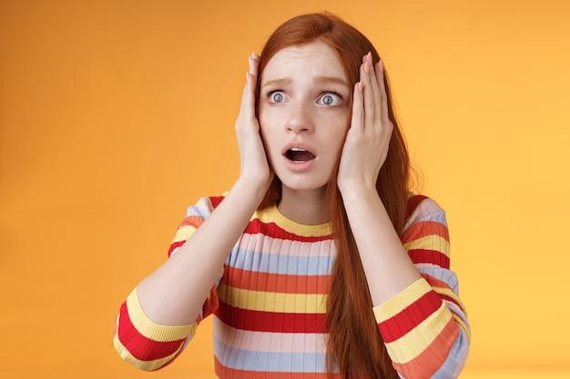 Sorge unsichere rothaarige europäische panische mädchen greifen kopf hände beide seiten keuchen offenen mund schockiert starren verängstigt verärgert beobachten schrecklichen unfall stehend besorgt orange hintergrund.