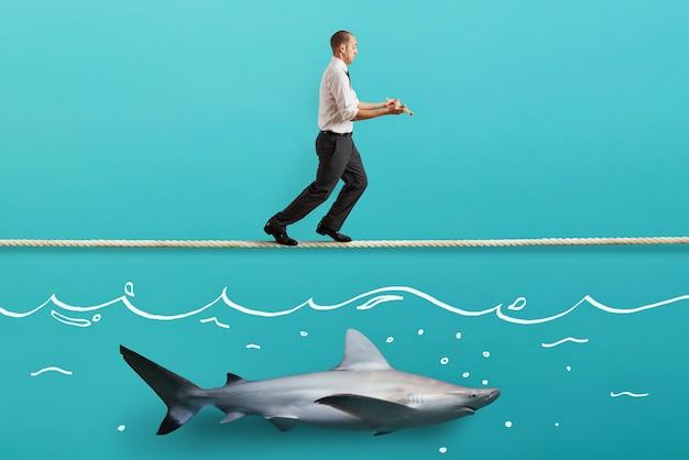 Sorgen mann im gleichgewicht, der auf einem seil über einem hai geht
