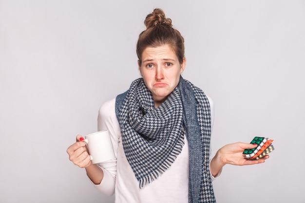Sorgen sie sich verwirrte frau, die tasse mit tee, viele pillen hält. studioaufnahme, auf grauem hintergrund isoliert