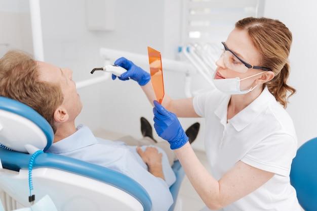 Sorgfältig qualifizierter arzt, der spezielle geräte verwendet, um ihre augen zu schützen und die zähne von männern weißer aussehen zu lassen