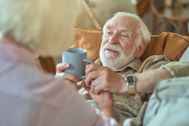 Sorgfältige ältere dame, die ihrem mann eine tasse tee gibt