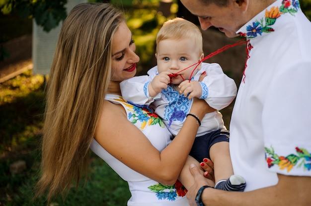 Sorgfältige eltern, die an hände ein baby anhalten, kleideten im gestickten hemd an