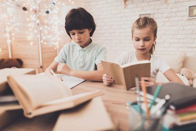 Sorgfältige intelligente kinder, die zu hause am schreibtisch lesen.