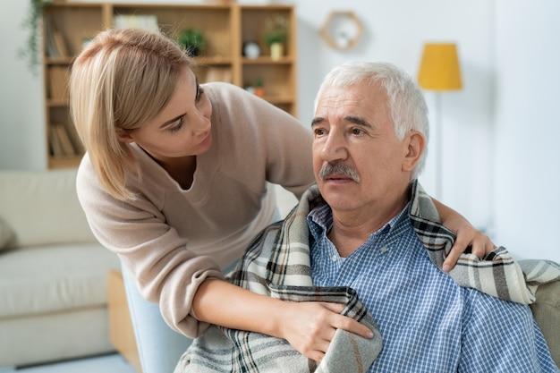 Sorgfältige und liebevolle tochter, die sich um ihren kranken älteren vater kümmert, während sie ihn zu hause in plaid einwickelt
