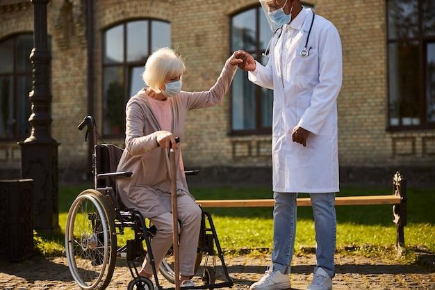 Sorgfältiger afroamerikanischer hausarzt, der eine ältere frau an der hand hält, während er sie aufrichtet