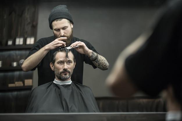 Sorgfältiger friseur mit großem bart und tätowierung kämmt die haare des bärtigen mannes im schwarzen haarschneideumhang im friseursalon