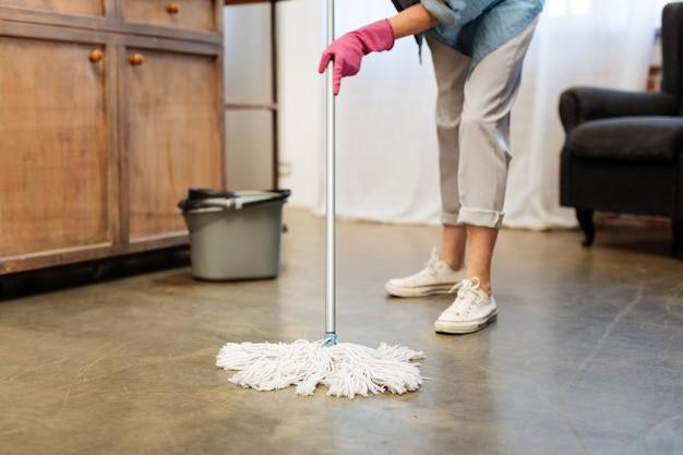 Sorgfältiges waschen des bodens. erwachsene putzfrau, die rosa gummihandschuhe trägt und einen stock ihres mopps trägt