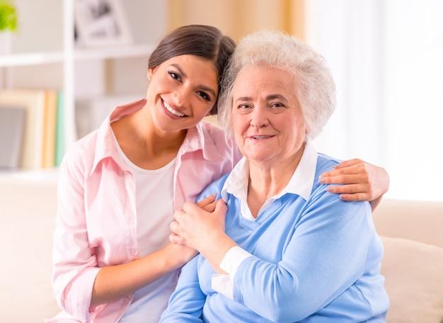 Sorgfalt der älteren frau zu hause sitzend auf der couch