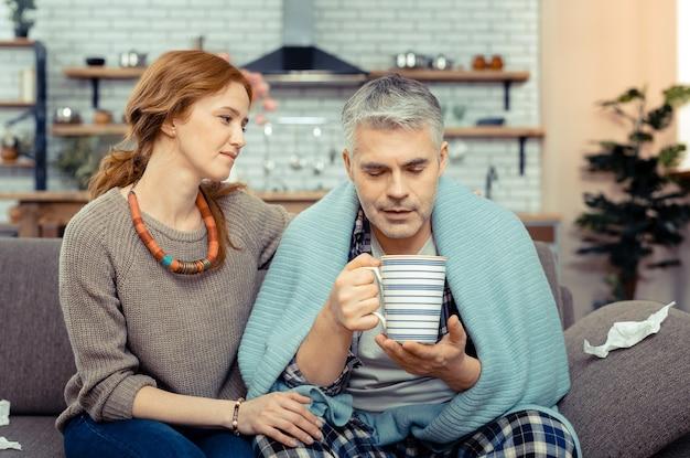 Sorgfalt und liebe. schöne nette frau, die ihren mann ansieht, während sie ihn während seiner krankheit unterstützt supporting
