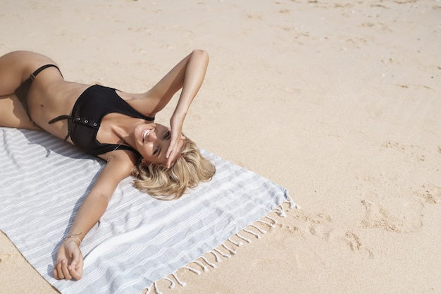 Sorglos entzückte gebräunte blonde junge frau liegt am sandstrand.