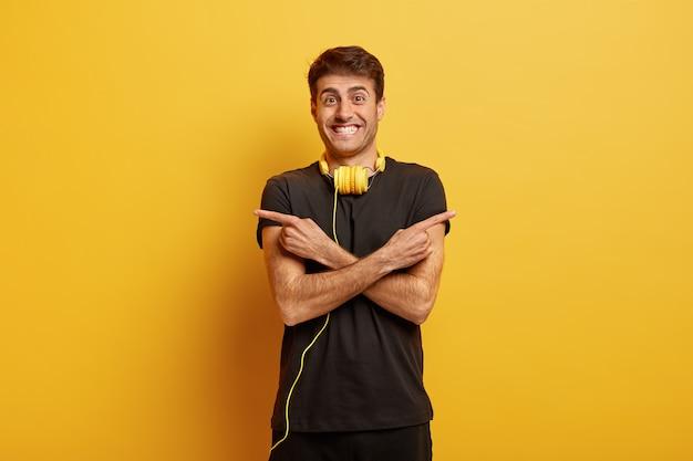 Sorglos geselliger mann kreuzt hände, zeigt auf verschiedene seiten, hat ein glückliches lächeln, trägt schwarze kleidung