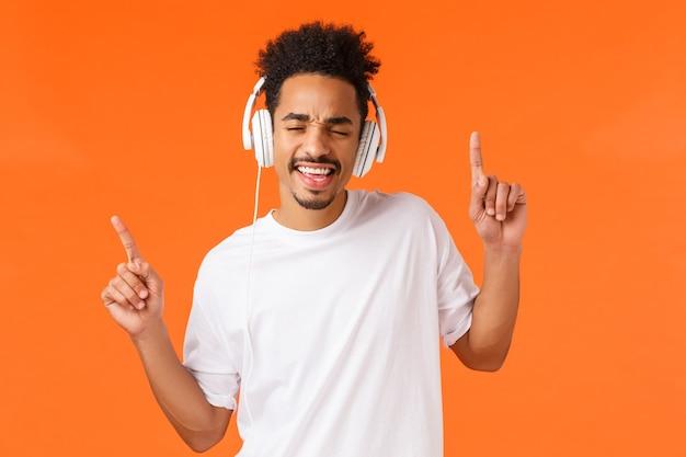 Sorglos glücklicher und erleichterter afroamerikanischer gutaussehender hipster-typ, der musik in kopfhörern hört, tanzt und hände in den rhythmus schüttelt, geschlossene augen, die in kopfhörern mitsingen, orangefarbener hintergrund