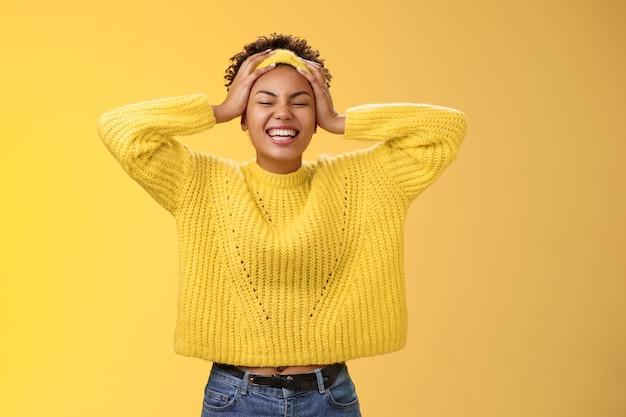 Sorglos glückliches afrikanisches mädchen in pulloverstirnband, das den kopf berührt und spaß beim lächeln hat, erleichtert aufgeregt, laut lachend, schließen die augen, die sich freuen, verbringen gute zeit beim feiern, stehen auf gelbem hintergrund.