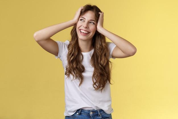 Sorglos glückliches attraktives lächelndes mädchen halten den kopf lockige frisur abbiegen obere linke ecke sonniger sommertag ausgezeichnete glückliche wochenenden stehen amüsiert aufgeregt abenteuer beginnen gelben hintergrund