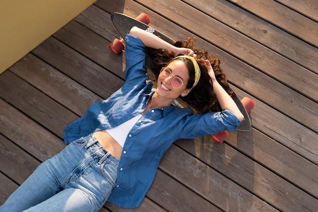 Sorglos lächelnde frau auf skateboard entspannt und glücklich trendige mädchen-skateboarderin, die auf longboard liegt