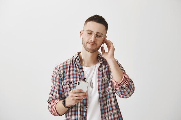 Sorglos lächelnder junger mann mit brille, die mit seinem telefon aufwirft