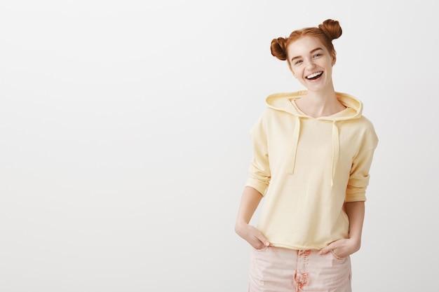 Sorglos lächelndes rothaariges mädchen mit albernem haarschnitt