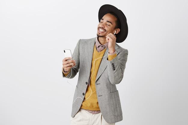 Sorglos tanzender afroamerikanermann, der musik in kopfhörern hört, lächelt und smartphone hält