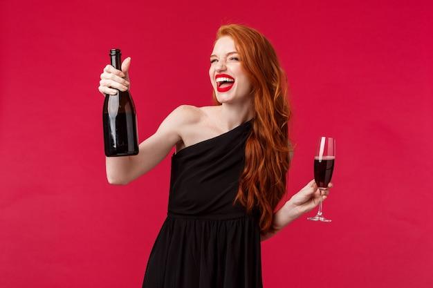 Sorglose aufgeregte schöne rothaarige frau, die nacht mit freundinnen feiert, am geburtstag oder im feiertag feiert, flasche champagner hält, der beifall aus glas trinkt, zufrieden wegschauen