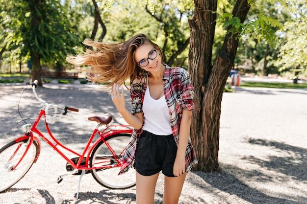 Sorglose blonde frau, die gutes sommerwetter genießt. außenaufnahme des atemberaubenden aktiven mädchens mit fahrrad.