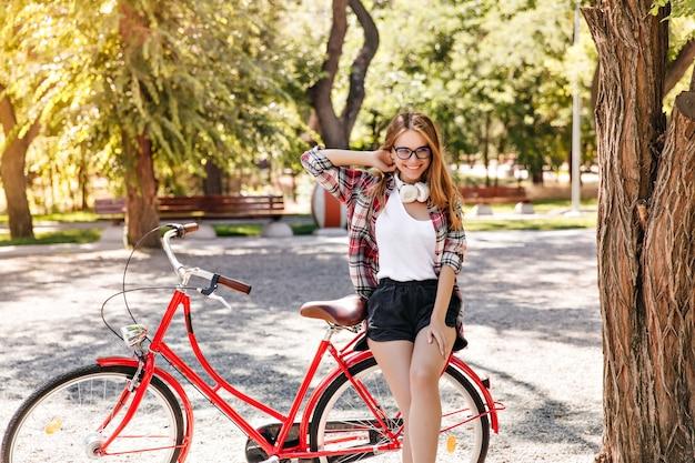 Sorglose blondhaarige frau mit rotem fahrrad, die das leben genießt. kaukasisches blondes mädchen, das freizeit im frühlingspark verbringt.