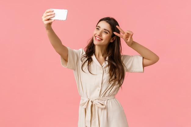 Sorglose emotionale, glücklich lächelnde brünette frau im kleid, telefon halten, selfie nehmen und friedenszeichen machen, kopf neigen und lächeln, positive stimmung an anhänger senden, rosa wand stehen