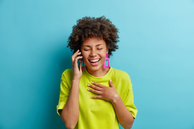 Sorglose entspannte positive afroamerikanerin lacht, während gespräche über das smartphone die hand auf der brust halten, die augen schließen, positive emotionen ausdrücken, lustige witze hören, lässig gekleidet, drinnen stehen
