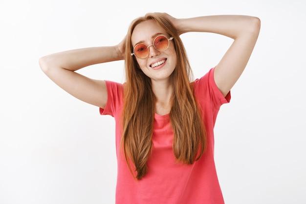 Sorglose entspannte und glückliche junge rothaarige frau, die trendige sonnenbrille und rosa t-shirt hält hände hinter kopf hält