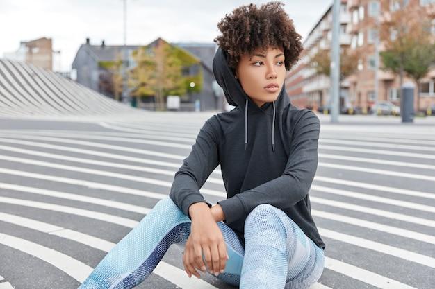 Sorglose ethnische junge frau trägt lässiges sweatshirt mit kapuze