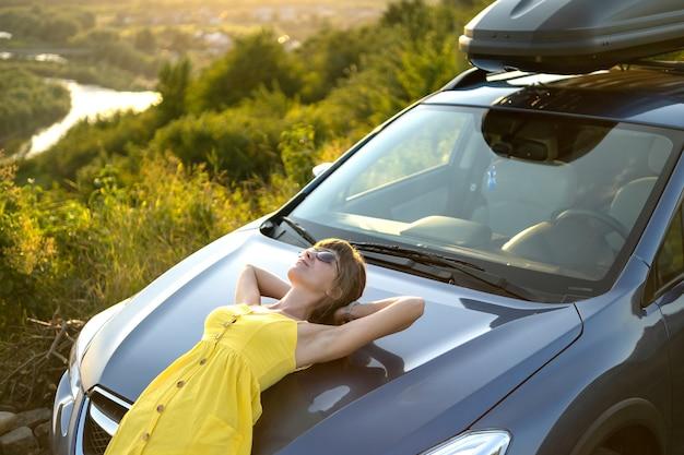 Sorglose fahrerin im gelben sommerkleid, die einen warmen abend in der nähe ihres autos genießt.
