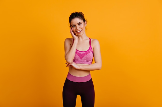Sorglose fitnessfrau, die mit lächeln aufwirft