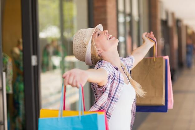 Sorglose frau, die einkaufstaschen hält
