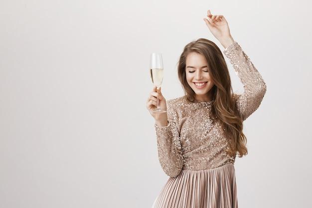 Sorglose frau, die im abendkleid tanzt und champagnerglas hält