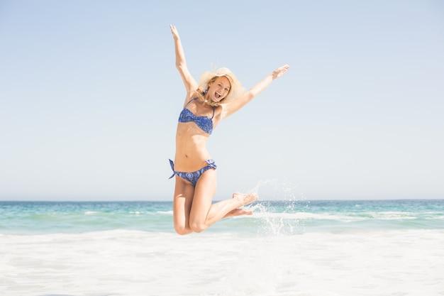 Sorglose frau im bikini, der auf den strand springt