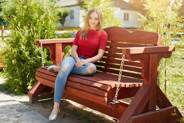 Sorglose frau mit glattem haar, das roten pullover und trendige jeans trägt, die an der bequemen holzbank im park sitzen und sonnenschein genießen