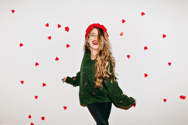 Sorglose frau mit lockigem hellbraunem haar, das am valentinstag mit geschlossenen augen lacht