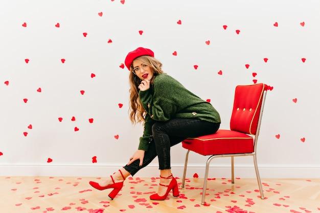 Sorglose frau trägt weiches grünes hemd, das im roten stuhl sitzt