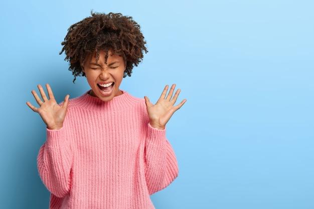 Sorglose freudige frau mit einem afro, der in einem rosa pullover aufwirft