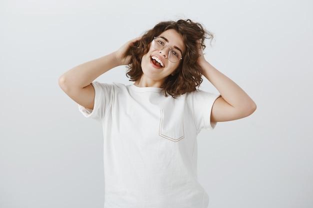 Sorglose glückliche frau in der brille, die ihren neuen haarschnitt mit erfreutem gesicht berührt