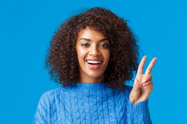 Sorglose, glückliche freudige frau des nahaufnahmeporträts, die feiertage feiert, allen ein gutes neues jahr wünscht, friedenszeichen zeigt und freudig lächelt, positivität und freude ausdrückt, pullover trägt.