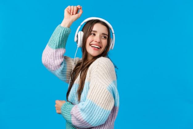 Sorglose, glückliche tänzerin des oberkörperporträts in den kopfhörern, lächelnd, hände oben frei und optimistisch anhebend, lieblingslieder genießend, spezielle winterferien playlisty und fröhlich lachen, blau