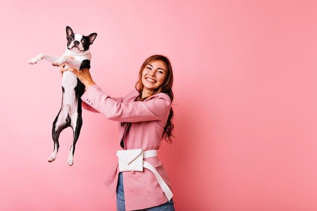 Sorglose junge dame, die schwarze französische bulldogge mit aufrichtigem lächeln hält. innenporträt des freudigen mädchens, das mit hund auf pastell spielt.