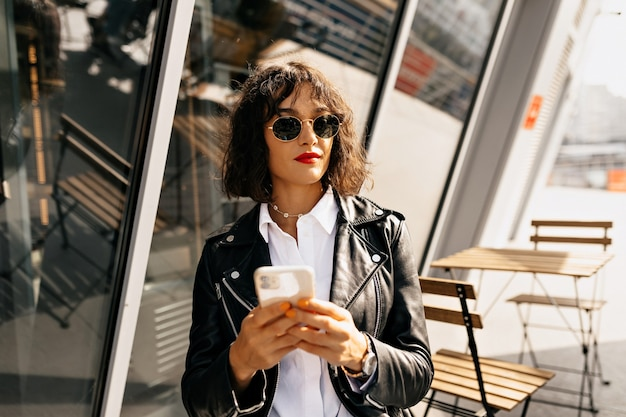 Sorglose junge frau im trendigen vintage-outfit, das auf terrasse sitzt