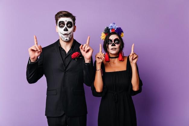 Sorglose junge leute in zombiekostümen, die lustige gesichter machen. europäische freunde, die an halloween erstaunen ausdrücken.