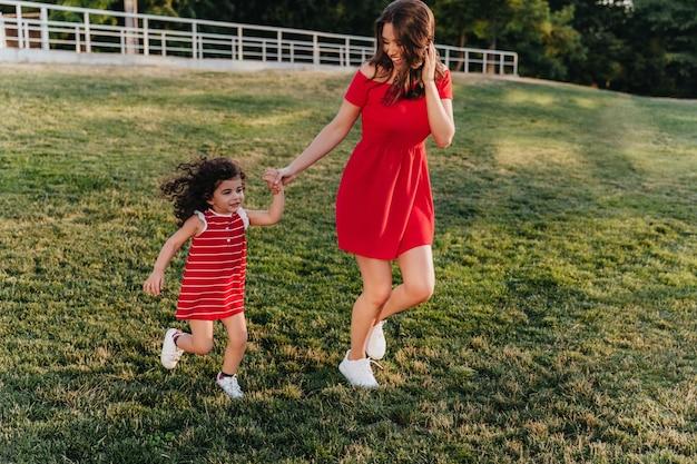 Sorglose junge mutter, die hände mit kind beim laufen um park hält. lustige frau im roten kleid tanzt mit ihrer tochter auf dem gras.