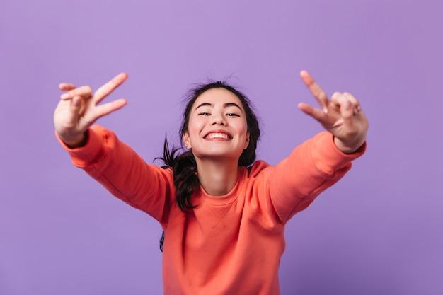 Sorglose koreanische frau, die friedenszeichen zeigt. studioaufnahme der glücklichen asiatischen brünettenfrau lokalisiert auf lila hintergrund.